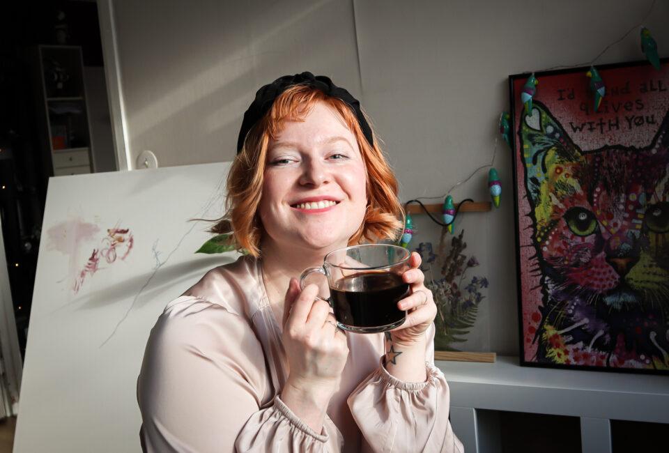 Glad redaktör dricker kaffe i solsken.